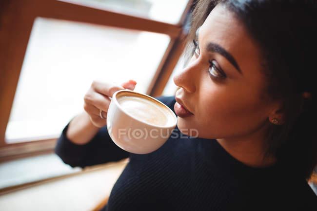 Donna premurosa che beve una tazza di caffè nel caffè — Foto stock