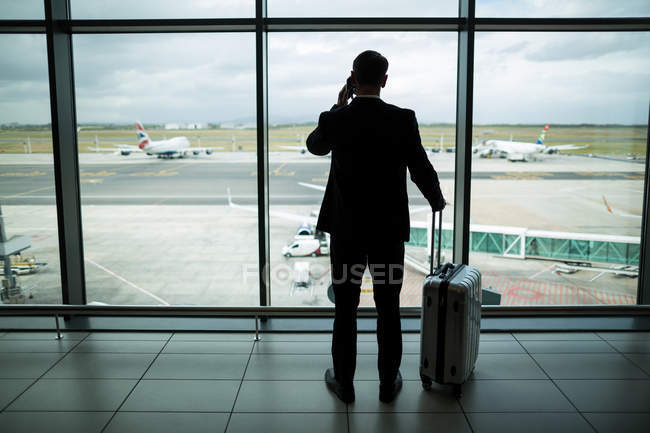 Rear view of businessman with luggage talking on mobile phone at airport — Stock Photo