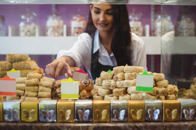 Verkäuferin arrangiert türkische Süßigkeiten an der Theke im Geschäft — Stockfoto