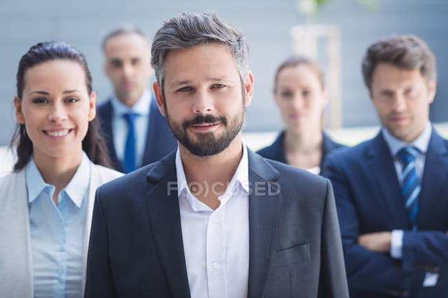Portrait of confident businessman with colleagues standing outside office building — Stock Photo