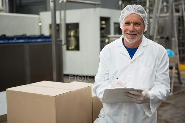 Портрет работника мужского пола, пишущего на блокноте на заводе холодных напитков — стоковое фото