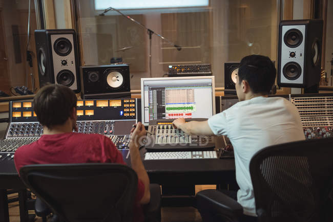 Аудиоинженеры используют звуковой микшер в студии звукозаписи — стоковое фото