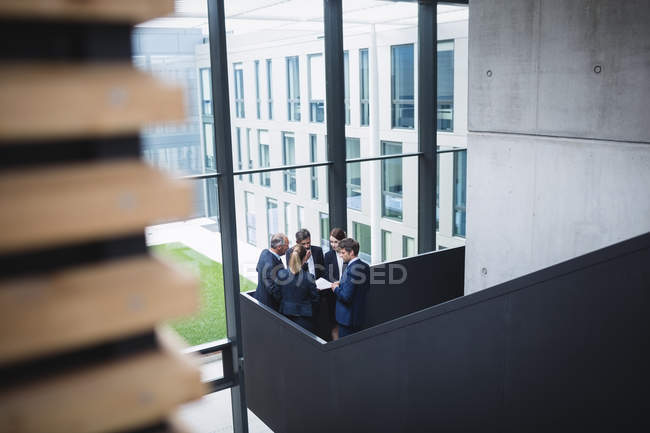 Group of business people having a discussion near staircase in office — стоковое фото