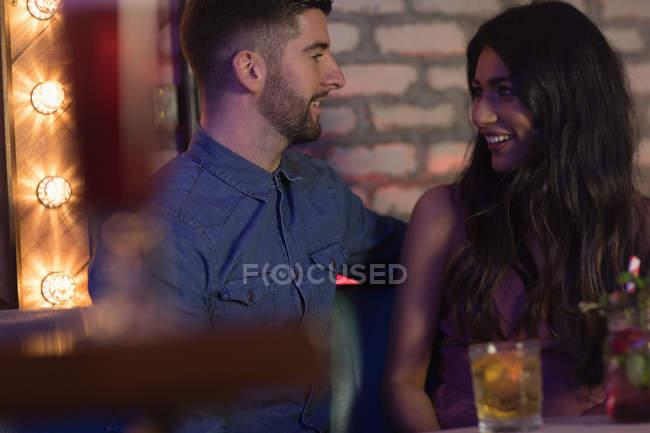 Smiling couple talking while enjoying drinks in bar — Stock Photo