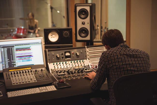Задний план звукоинженера с помощью звукового миксера в студии звукозаписи — стоковое фото