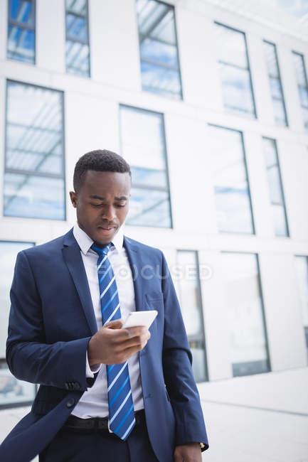 Бизнесмен с помощью мобильного телефона вне Офисное здание — стоковое фото