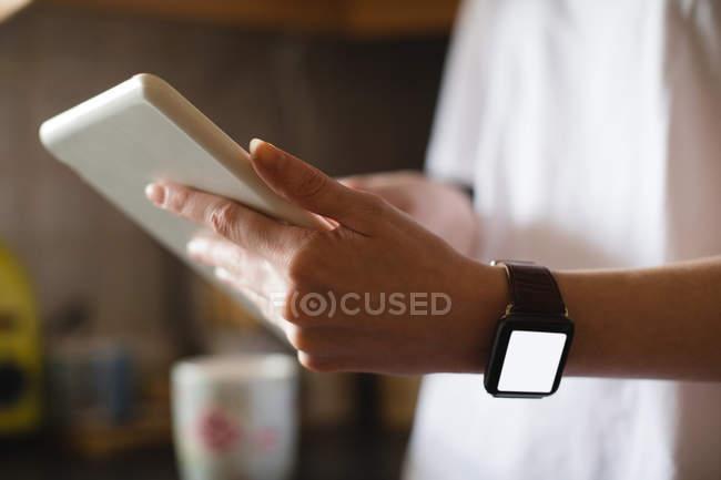 A meio da seção da mulher usando tablet digital na cozinha em casa — Fotografia de Stock