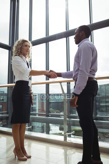 Dirigenti di affari che stringono la mano a corridoio di ufficio — Foto stock