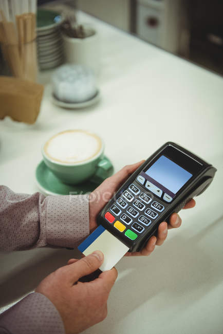 Close-up of hands making payment through credit card in cafe — Stock Photo