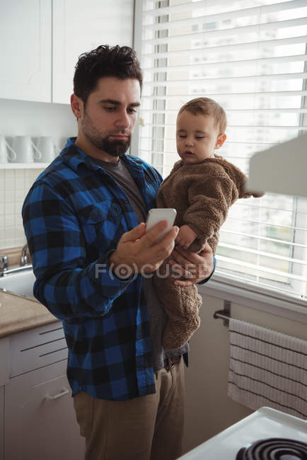 Father using mobile phone while holding his baby in kitchen at home — Stock Photo