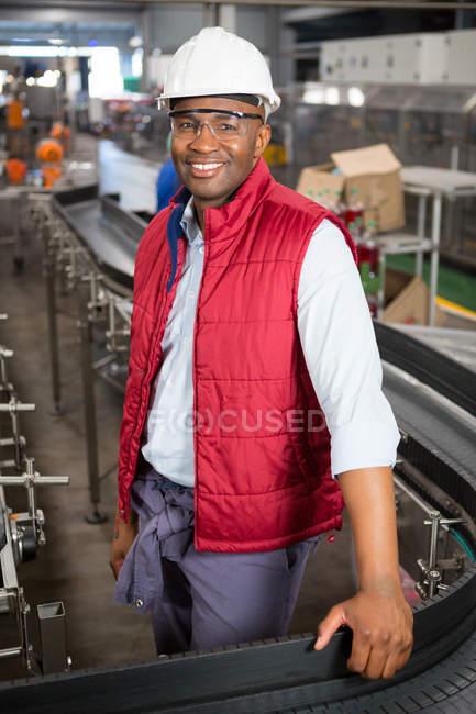 Портрет счастливого работника-мужчины, стоящего на конвейере на заводе — стоковое фото