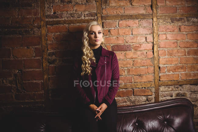 Beautiful woman sitting on sofa against brick wall — Stock Photo