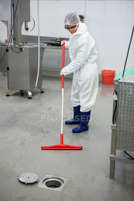 Female staff cleaning the floor at meat factory — Stock Photo