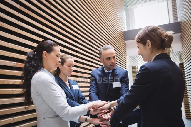 Negócios pessoas empilhamento mãos juntos no escritório — Fotografia de Stock