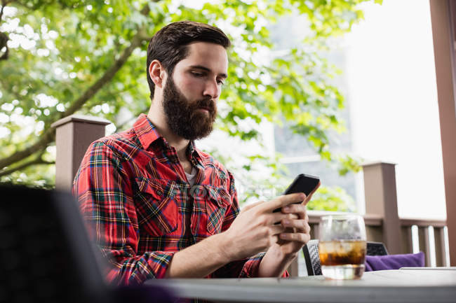 Людина за допомогою мобільного телефону, сидячи в барі — стокове фото