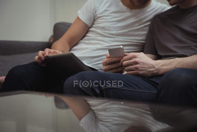 Schwules Paar sitzt auf Sofa und schaut zu Hause auf digitales Tablet — Stockfoto