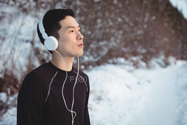 Thoughtful man listening to music in headphones during winter — Stock Photo