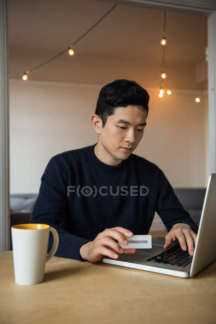 Man doing online shopping on laptop at home — Stock Photo