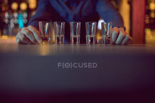 Bartender placing shot glasses in a row at counter in bar — Stock Photo
