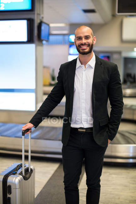 Portrait of businessman standing with luggage at waiting area in airport — Stock Photo