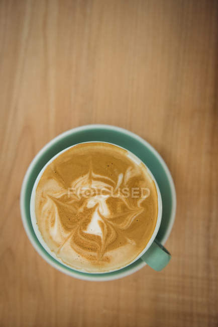 Cup of coffee on wooden table in coffee shop — Stock Photo