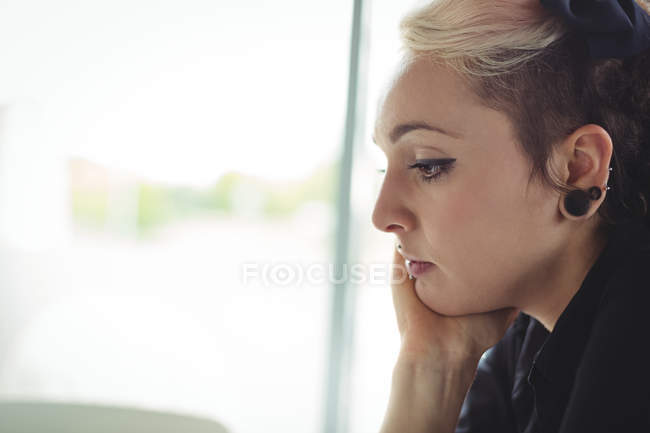 Thoughtful woman with hand on chin in cafe — Stock Photo