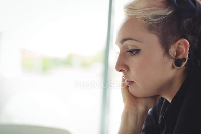 Продуманий жінка з руки на підборідді в кафе — стокове фото