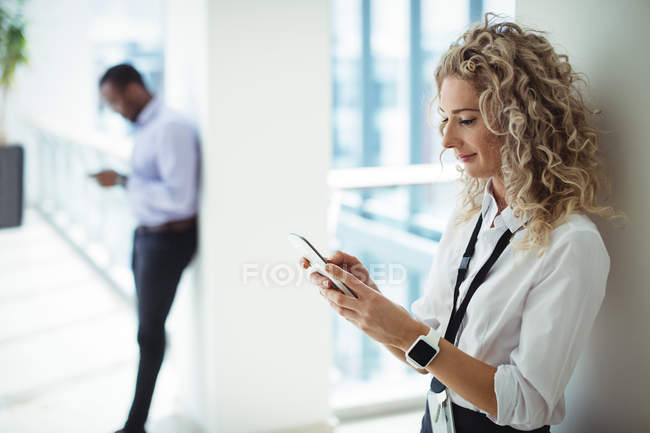 Блондинка, использующая мобильный телефон в офисном коридоре — стоковое фото