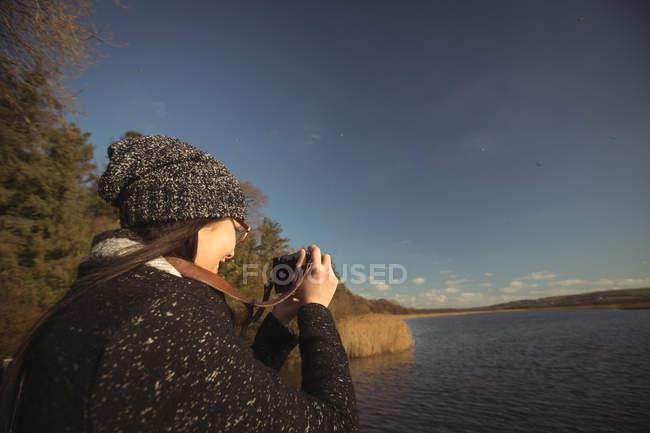 Жінка, беручи фотографії цифрової камери на сонячний день в парку — стокове фото