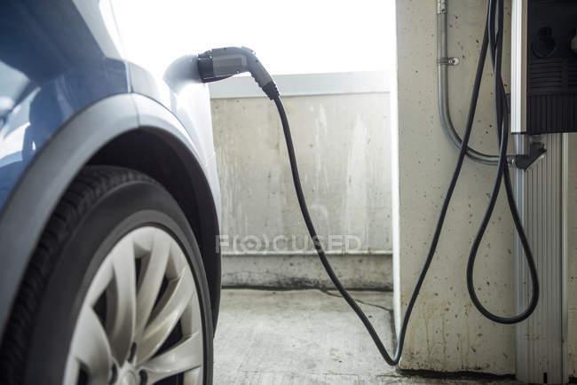 Gros plan de la recharge de voiture avec chargeur de voiture électrique à la station de recharge — Photo de stock