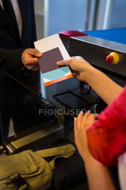 Close-up de funcionários do sexo femininos, dando o cartão de embarque para os passageiros no terminal do Aeroporto — Fotografia de Stock