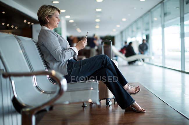 Donna d'affari che utilizza il telefono cellulare in sala d'attesa presso il terminal dell'aeroporto — Foto stock