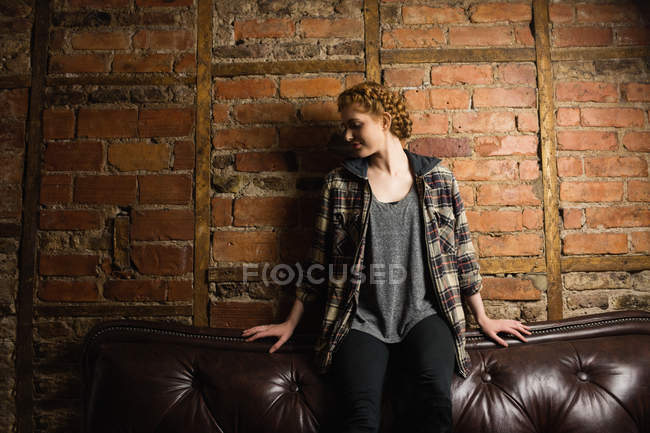 Beautiful woman sitting on sofa against brick wall — Stock Photo