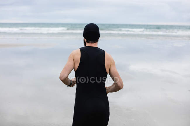 429b7eee9c7 Rear view of man in swimming costume and swimming cap running on beach —  Stock Photo