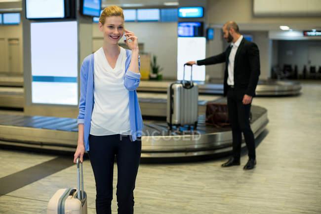 Empresária de pé com bagagem conversando no telefone celular na área de espera no terminal do aeroporto — Fotografia de Stock