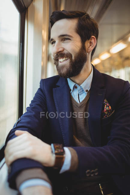 Smiling businessman looking through train window — Stock Photo