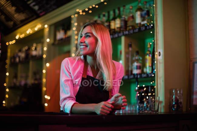 Beautiful smiling waitress leaning at bar counter — Stock Photo