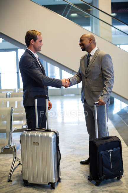 Business people shaking hand in waiting area with airport — Stock Photo