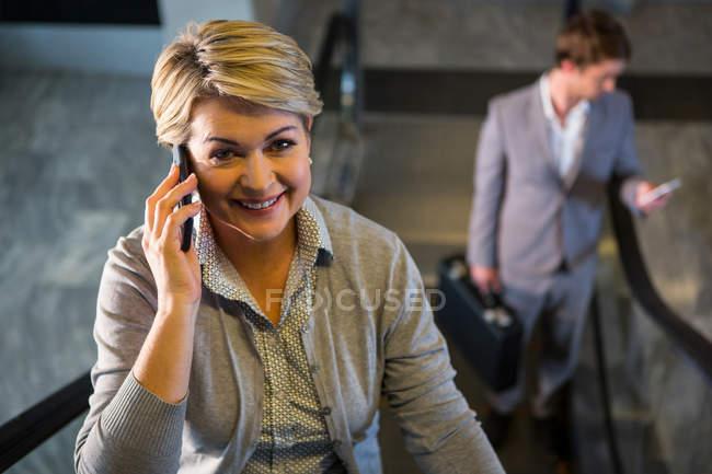 Empresária na escada rolante conversando no telefone celular no aeroporto — Fotografia de Stock