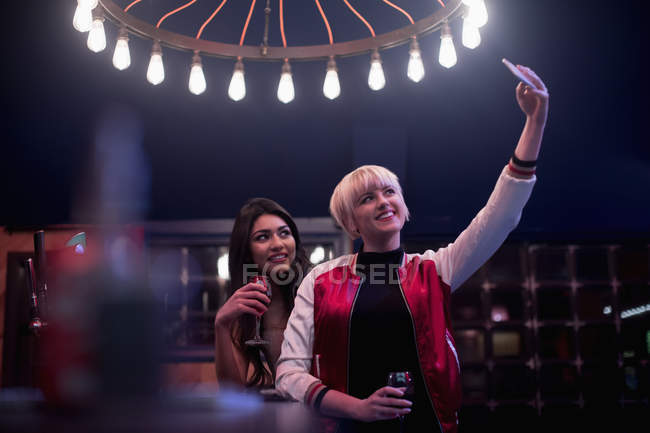 Smiling friends taking selfie while having wine in bar — Stock Photo