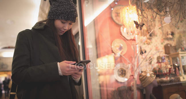 Smiling woman using mobile phone at the supermarket — Stock Photo