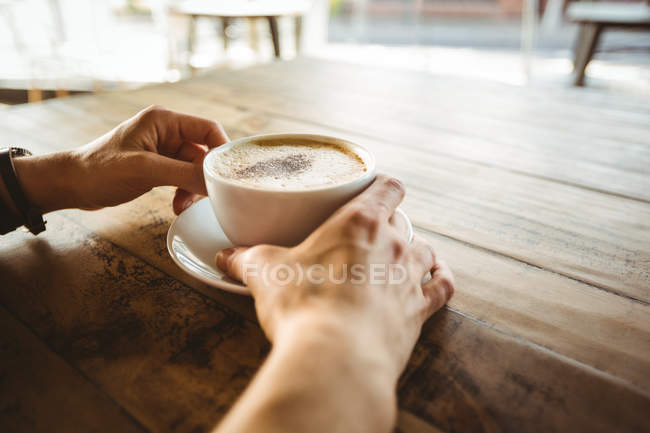 Hands of woman holding cup of coffee in cafe — Stock Photo