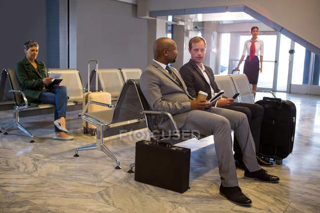 Бизнесмен, взаимодействующий в зоне ожидания аэропорта — стоковое фото