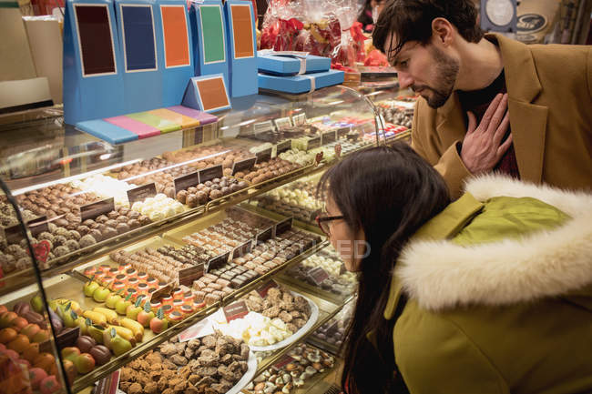 Couple looking at desserts at dessert counter in the supermarket — Stock Photo