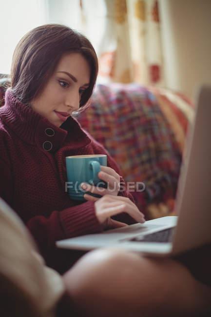 Belle femme prenant un café tout en utilisant un ordinateur portable sur le canapé à la maison — Photo de stock