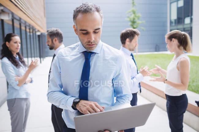 Бізнесмен, використовуючи ноутбук за межами Офісна будівля — стокове фото