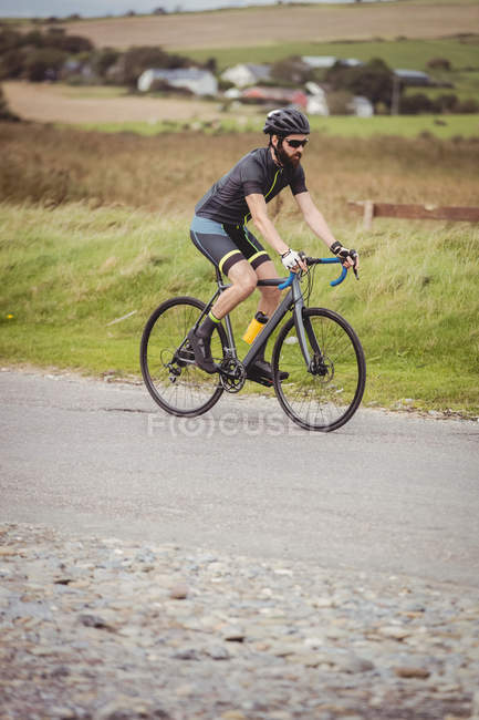 Спортсмен на велосипеде по сельской дороге — стоковое фото