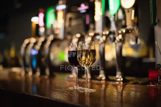 Glasses of red and white wine on bar counter at bar — Stock Photo