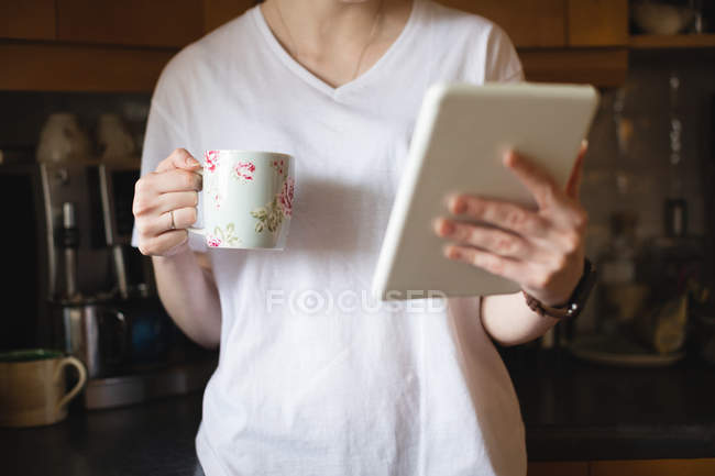 Mid-section of woman using digital tablet while having coffee in kitchen at home — Stock Photo