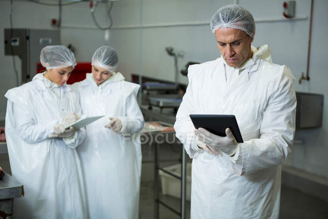 Technicians using digital tablet at meat factory — Stock Photo